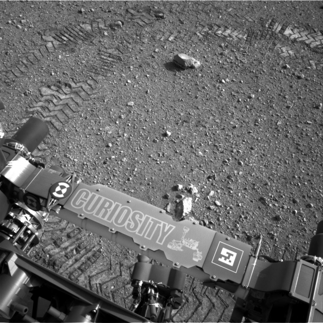 Curiosity Leaves Its Mark, This image shows a close-up of track marks from the first test drive of NASA's Curiosity rover. The rover's arm is visible in the foreground. A close inspect...