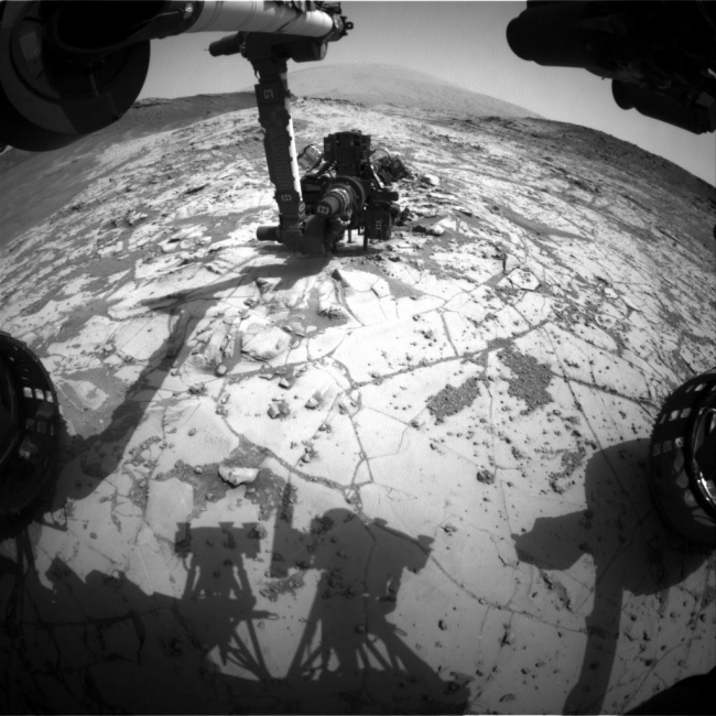 Curiosity Conducting Mini-Drill Test at 'Mojave', This view from the wide-angle Hazard Avoidance Camera (Hazcam) on the front of NASA's Curiosity Mars Rover shows the rover's drill in position for a mini-dri...