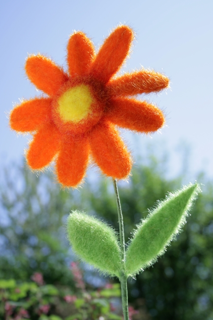 Artificial orange flower, An artificial orange flower with green leafes against a blurry background of sky and green
