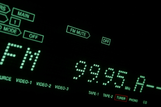 Green Hi-Fi LCD display in close-up TUNER/FM, A hi-fi receiver's green dot-matrix LCD display in extreme close-up showing FM 99.95 (tuner). Tilted view with green font on black background.