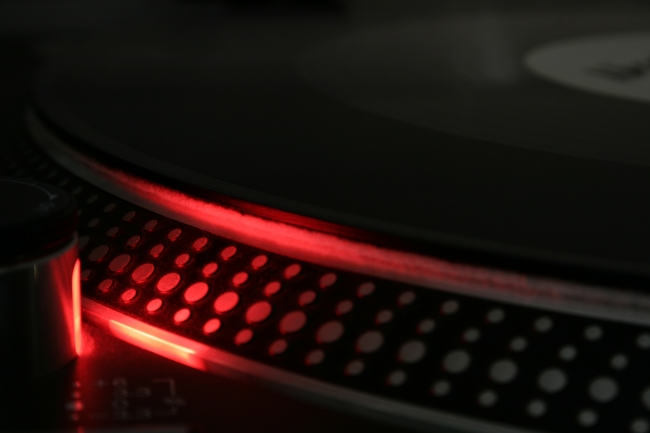 Turntable rim close-up at the speed control, Close-up of the speed control section, the left platter rim on a Technics SL-1210MK2 DJ turntable, illuminated by the red light of the strobe.