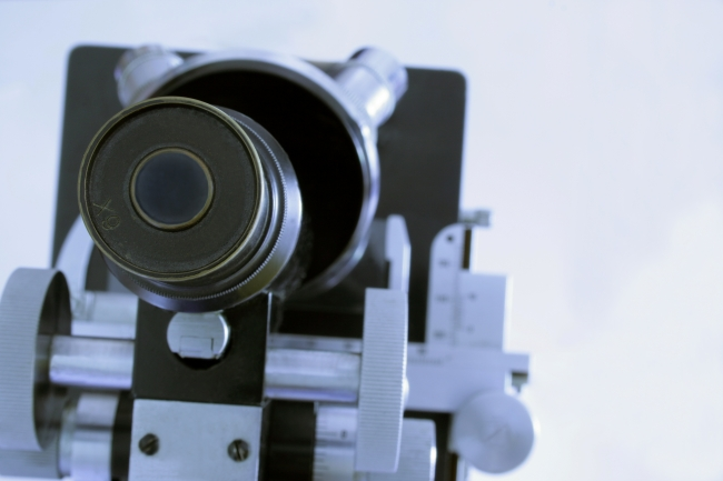 Looking down the microscope, A black and silver microscope, viewpoint from top-down, as if looking into the ocular, crisp focus on the viewfinder / eyepiece