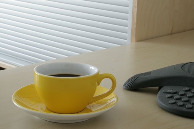 Yellow cup filled with coffee on a table next to a Polycom conference phone,