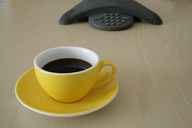 Cup of coffee on a conference table with a Polycom phone,