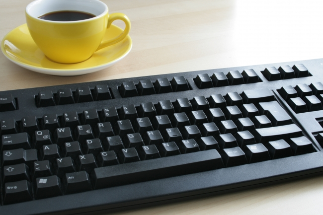 Cup of coffee on a table next to a black Cherry keyboard,