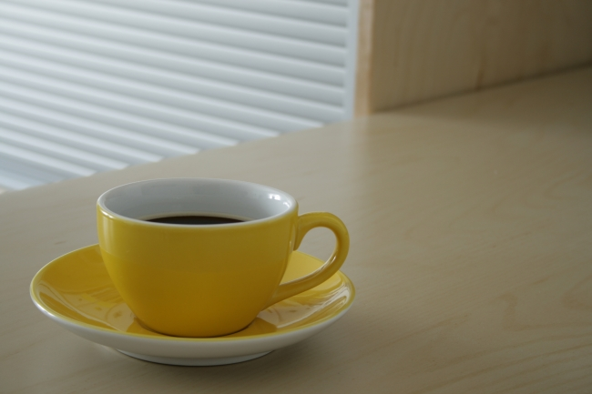 Yellow cup of coffee on wooden table, Yellow cup of coffee on wooden table. In the background a modern piece of office furniture provides a lined pattern out of focus