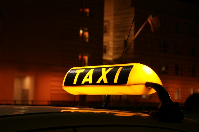 Illuminated Taxi sign, Illuminated TAXI sign on car cab waiting for a fare in the city at night, seen in front of the Berlin US Embassy