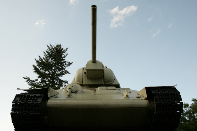 T-34 tank from low angle, Near the German Reichstag in Berlin as part of the Sowjetisches Ehrenmal, a T-34 tank, frontal from a low angle against sky and cedars