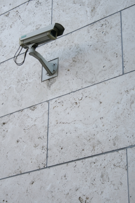 Surveillance camera in waterproof housing, A modern surveillance camera in water-proof housing mounted on a large tiled government building wall