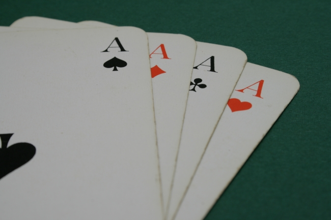 Cards, all aces, on green, a selection from a complete deck of gaming cards