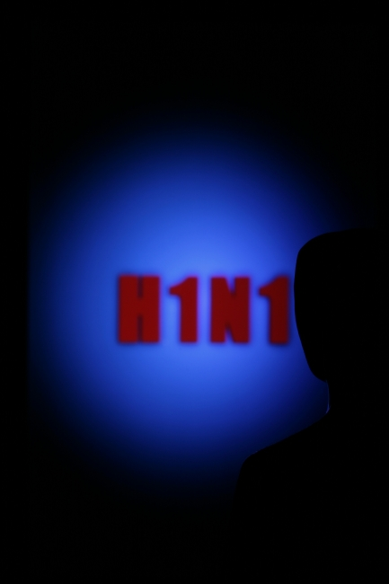 Looking towards H1N1, A man is looking into a room where on blue background H1N1, the abbreviation of the swine flu influenza virus, is written in red glowing letters.