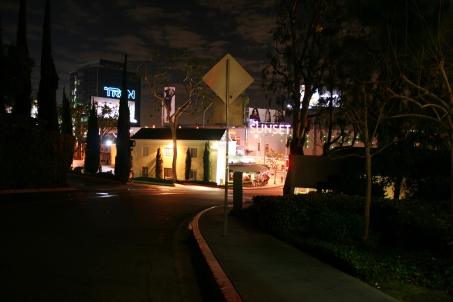 """W Sunset Blvd seen from Sunset Plaza Drive at night, The giant TRON billboard and """"The Sunset"""" Sunset Plaza mall"""