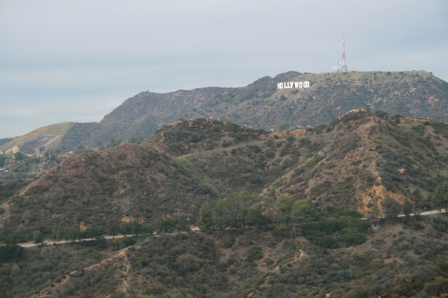 The Hollywood sign as seen from Griffith Park Observatory, in dim evening sunlight