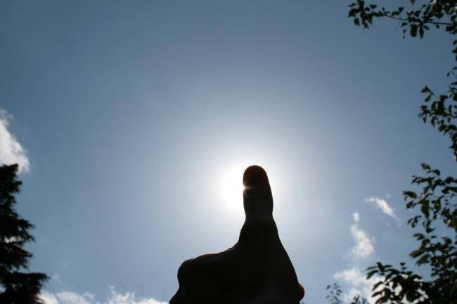 Daumen gegen die Sonne,