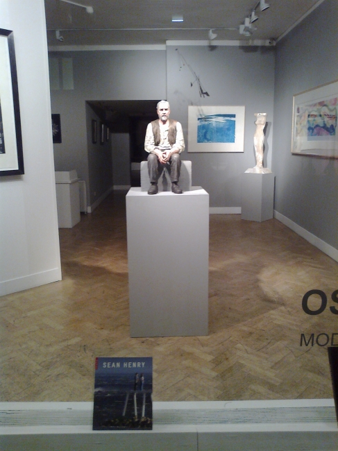 Man sitting on bloc, in a gallery's window